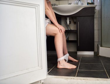 A woman sitting on the toilet at home suffering from constipation from iron supplements