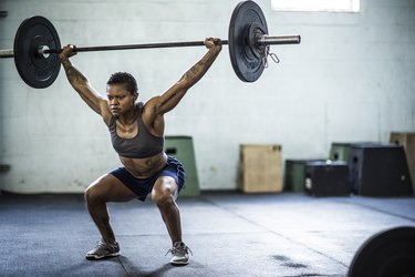 woman doing an overhead barbell squat in the gym as part of a superset workout