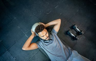 Handsome black man lying on floor working out with a med ball his abs