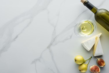 top view of glass of wine, cameembert cheese pieces, figs and pears on white marble tabletop