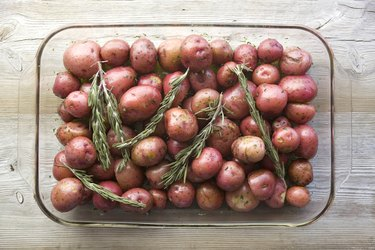 Small red potatoes with rosemary in a roasting dish ready for oven roasting