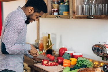 An African-American man cutting a bell pepper in his kitchen
