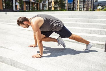 Young man exercising outside. Athletist doing mountain climber training. Exercising alone in horizontal position at urban building. Strong powerful athletist.