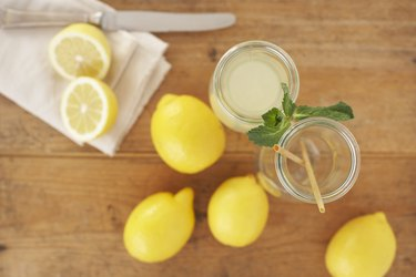 Carafe of lemon juice, sliced and whole lemons on wood, elevated view