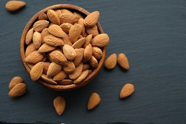 Almonds nut close-up.Raw almonds in a round wooden cup on a black slate background. Nuts in a cup.Vegetarian and vegan food.