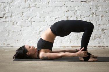 Young yogi attractive woman in Glute Bridge pose, loft background
