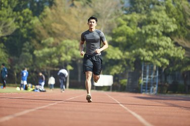 young asian athlete training on running track