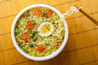 chopsticks and cup of instant noodles with boiled egg, peas and carrots