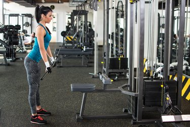 Beautiful girl doing triceps push down in gym.