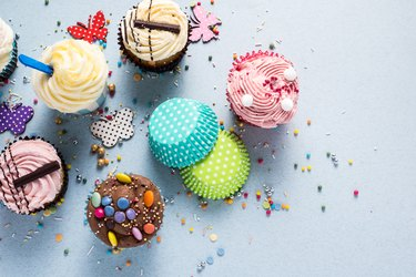 Vibrant cupcakes on blue background, party food concept