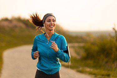 Happy female runner jogging in the morning in nature.
