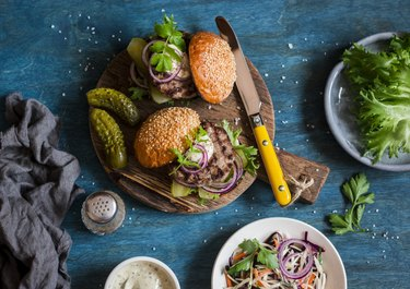Two homemade burgers on a wooden cutting board