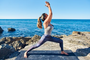 Beautiful young woman practicing yoga lunges on seaside against blue sea.