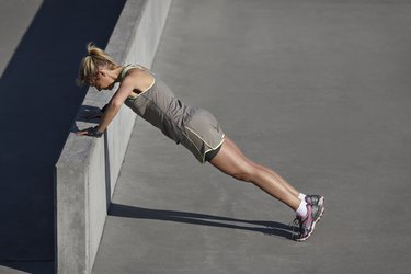 Woman doing pushups at urban setting