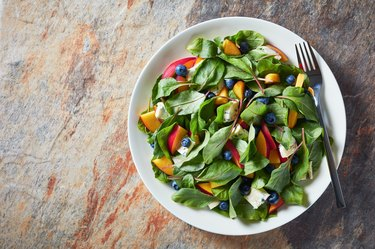 healthy salad with fresh chard leaves, peach, blueberries, pieces of cheese