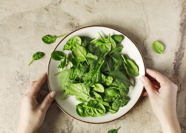 Woman's hands holding a plate with fresh spinach.
