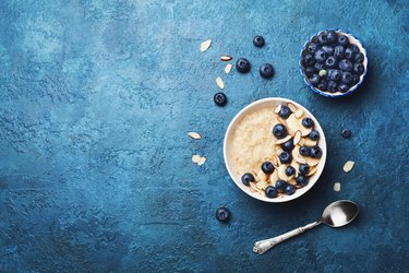 Bowl of oatmeal porridge with banana and blueberry on vintage table top view in flat lay style. Healthy breakfast.