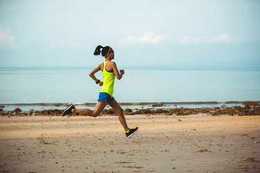 Young fitness woman running on beach