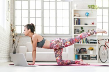 Young sporty attractive woman practicing yoga, doing a live-stream workout from her laptop