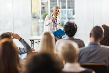 Adult doctor teaching on a seminar in a board room.