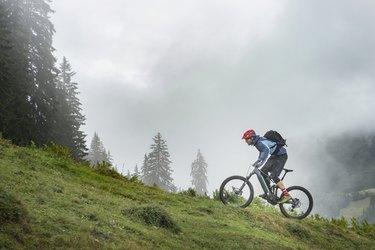 Man with Pedelec riding uphill in mountains, Saalfelden, Tyrol, Austria
