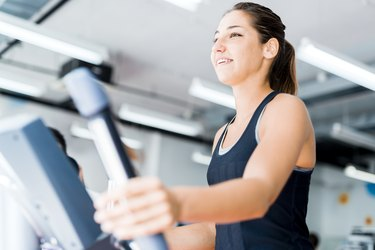 Beautiful young lady using the elliptical trainer