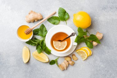 White Cup with natural herbal tea ginger lemon mint and honey. Gray background Copy space.