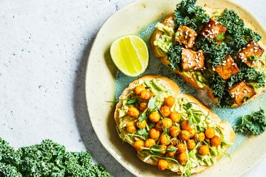 Vegan open sandwiches for bone health with guacamole, tofu, chickpeas and sprouts on a plate.