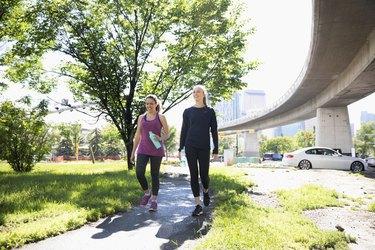 Women walking on sunny, urban path