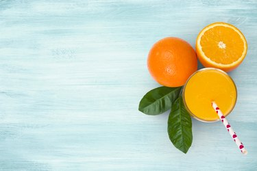 Orange juice glass and fruits on blue wooden tropical background