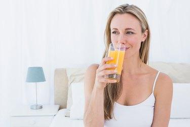 Woman drinking glass of vitamin C orange juice before going to sleep