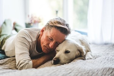 Retired man sleeping with dog comfortably on bed at home
