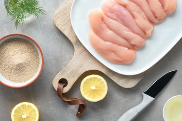 Raw chicken fillet. Meat with breadcrumbs, herbs , lemon and cooking oil. Top view on light
