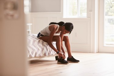 Young black woman sitting on her bed tying her sneaker