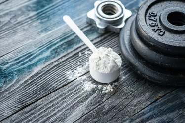 Classic dumbbell with pre workout powder on rustic wooden table