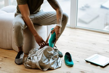 Dark-skinned sportsman with tattoo putting sneakers into bag