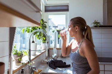 Side view of woman in sports clothing drinking water at kitchen