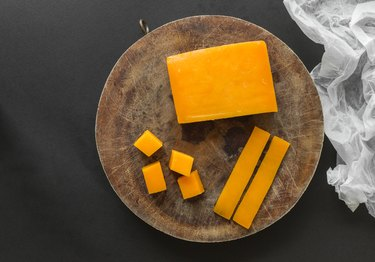 Block, slices and cubes cheddar cheese on a wooden cutting board