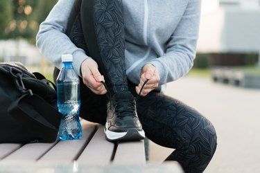 Shot of athletic woman tying she is shoelaces before a run.
