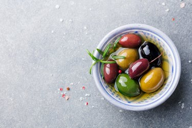 Olives assortment in bowl with oil.