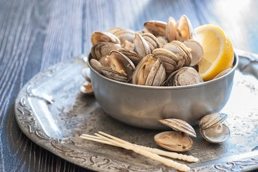 A bowl of vitamin B12-rich steamed clams on table.