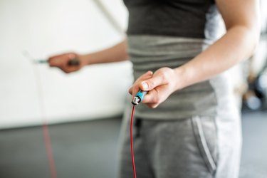 Woman hands holding skipping rope in the gym