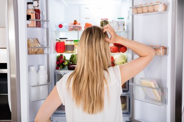 Rear view of a hungry woman looking in the fridge for something to eat