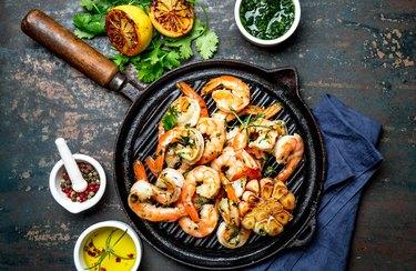 Grilled shrimps prawns on vintage grill pan, top view. Dark background