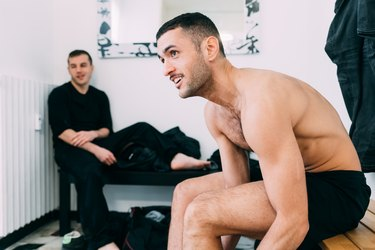 Men on benches in changing room