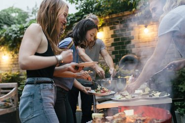 A Group Of Friends Helping Themselves To Food At A Summer Barbecue