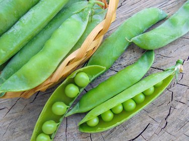 young green peas in pods in a basket on a wooden surface