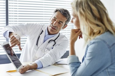 Doctor showing cholesterol levels to female patient