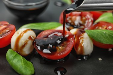 Pouring balsamic vinegar onto fresh vegetable salad on plate, closeup
