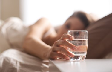 A woman in bed reaching for a glass of water